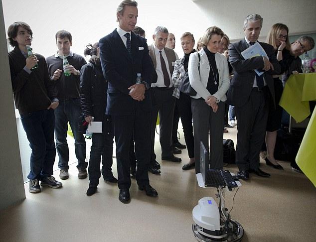 Filántropo multimillonario suizo Ernesto Bertarelli, cuarto desde la izquierda, sigue a un robot controlado por Mark-Andre-Duc, un paciente tetrapléjico en la parte del Instituto Federal Suizo de Tecnología en Lausanne, Suiza