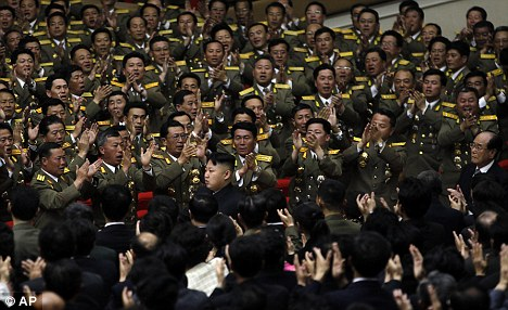 We're behind you: Kim Jong Un is applauded by military officers as he arrives at a concert today to mark the 80th anniversary of the founding of the North Korean army in Pyongyang