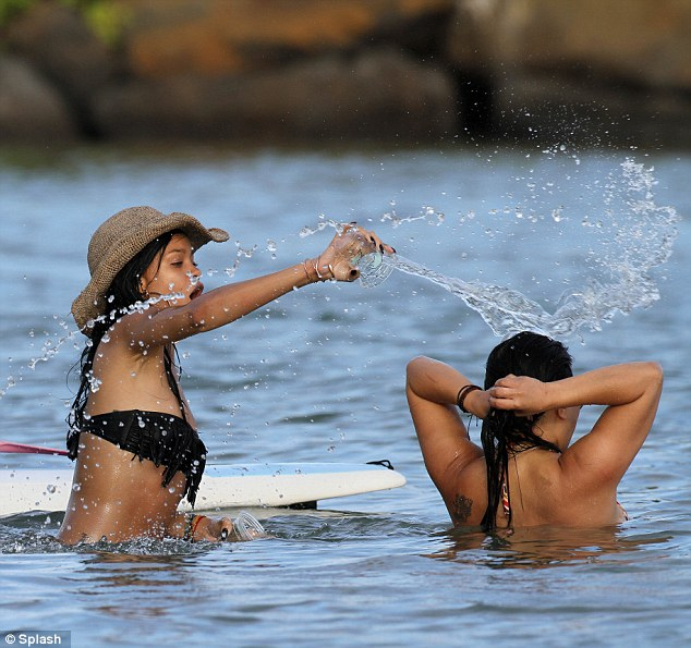 The drink's on you: Rihanna pours a cup of water over her friend's head