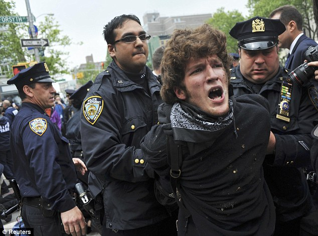 Taken down: An Occupy Wall Street demonstrator is arrested by the NYPD while marching in the Lower East Side of New York