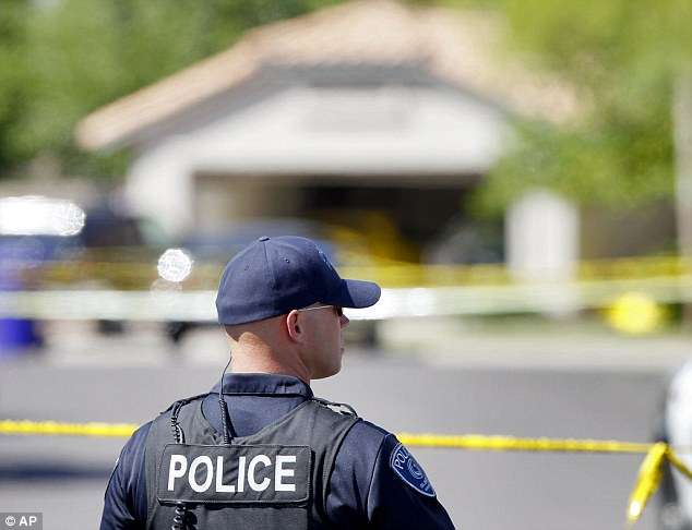 A Gilbert police officer stands outside the police tape outside a crime scene Wednesday, May 2, 2012 in Gilbert, Arizona