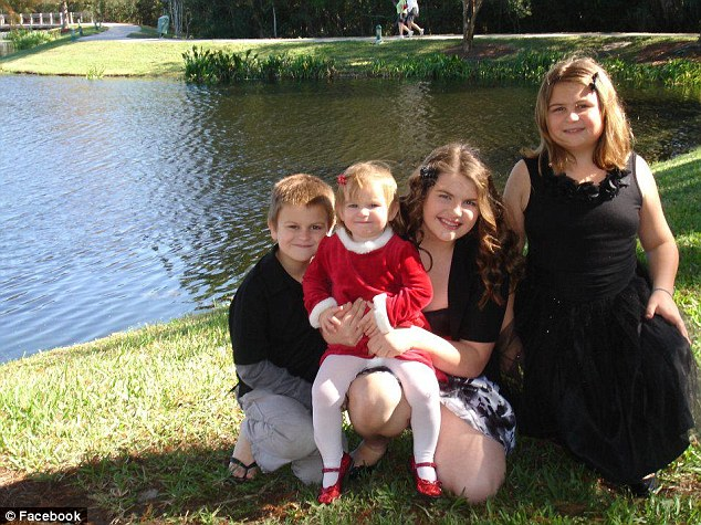 New home: Lou Lambros' four children posed in front of the lake by their house; they had moved in only two months before