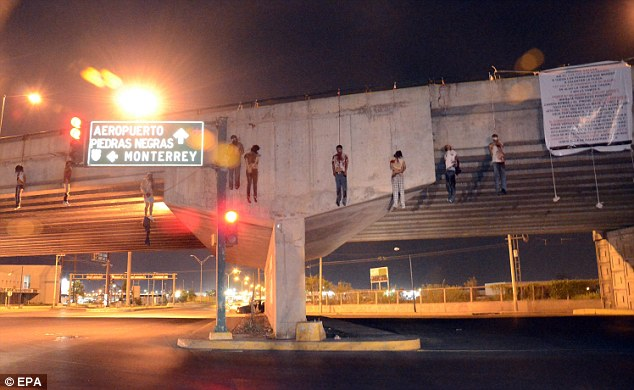 Gruesome: Nine bodies have been found hanging from a bridge in Nuevo Laredo, Mexico, which borders Texas. The four women and five men are suspected members of Los Zetas drugs cartel
