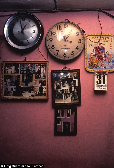 A wall in a house is adorned with clocks and pictures of relatives