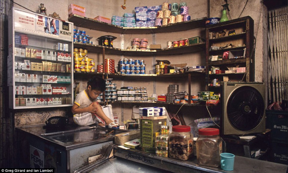 A child with a grazed knee sits on a counter top in a tiny shop which sells essentials like toilet paper and canned foods. Cigarettes are also on display in a cabinet