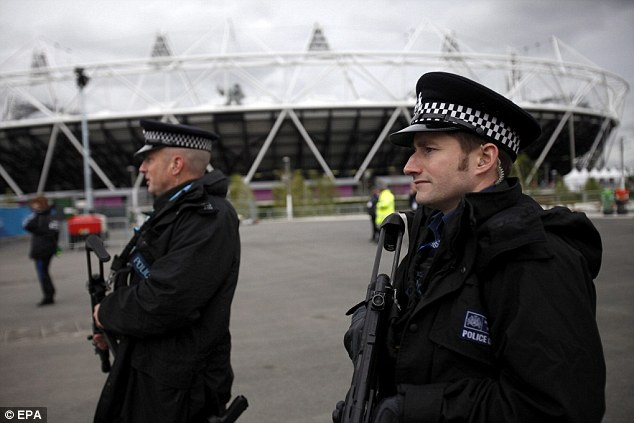 Watch out: Armed police officers patrol outside the Olympic stadium in the Olympic Park, London