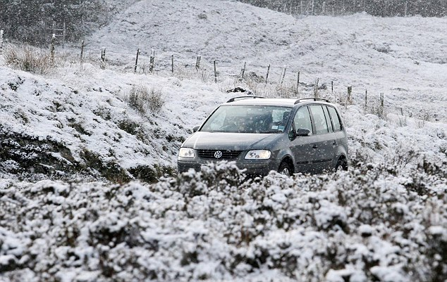 Snow in May: A car travels through appalling weather along the Inverness-Ullapool Road in Scotland