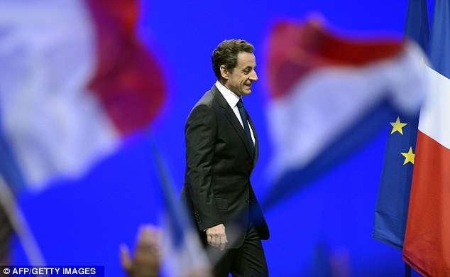 Putting a brave face on it: Sarkozy arrives to address his supporters after the result reaches crowds at La Mutualite hall in Paris
