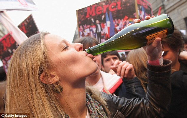 Bottoms up: A young Socialist supporter celebrates the party's win with a drink on the streets of Paris