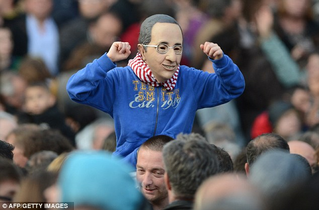 Face of a new France: A boy wears a rubber mask of Hollande's face during celebrations in Tulle