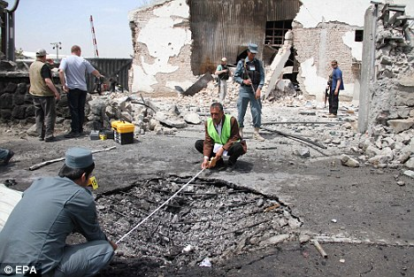 Hugh blast: Afghan security officials measure the crater formed at the scene of a suicide bomb attack in Kabul on May 2