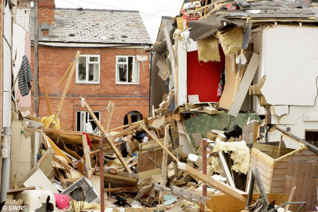 Jumble: The remains of the woman's possessions are visible amongst the rubble of her Cheltenham home