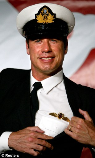 Flying high? John Travolta shows off his pilot's 'wings' which entitle him to fly a jumbo jet