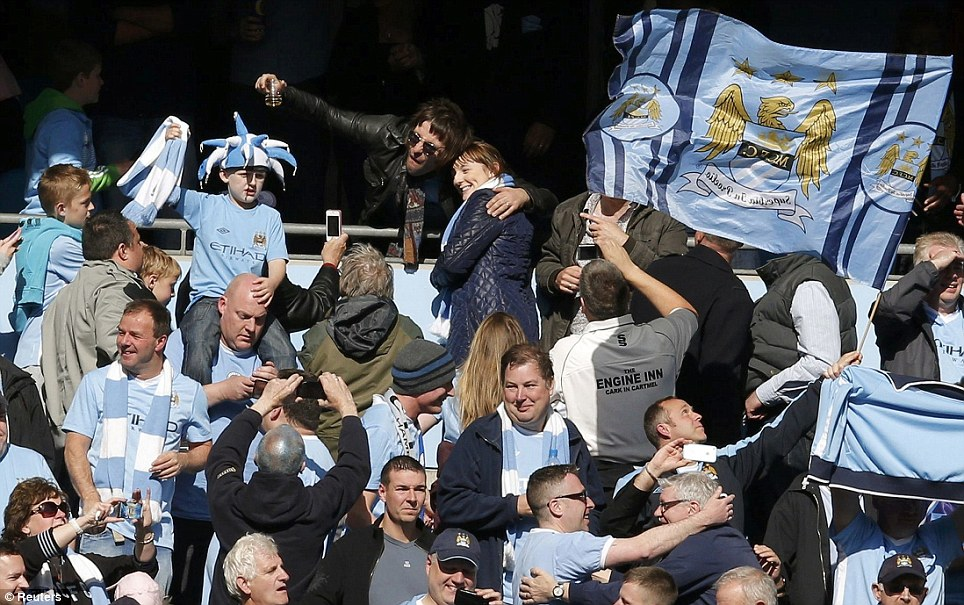 Star showing: Liam Gallagher (top middle) celebrates with the City fans at the end of the match