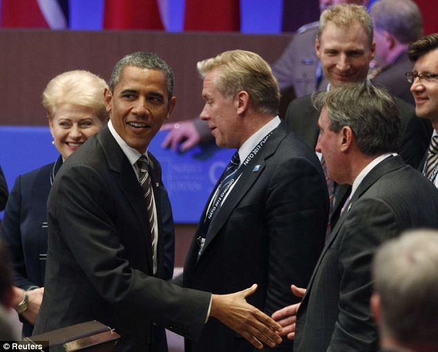 All smiles: Mr Obama greets participants during the Meeting with Partners event at the Nato Summit. Despite his remarks, experts warned that it was unrealistic to expect Afghanistan to be completely free of terrorism
