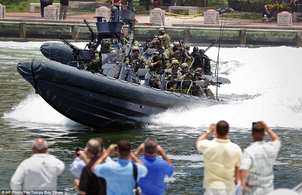 With guns raised and helmets on, the marine assault team take to the water in a speed boat