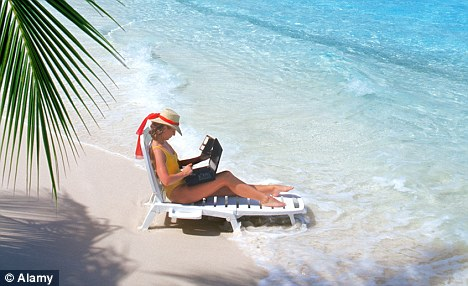 Woman sitting on sandy shore on beach chair with laptop