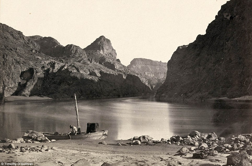 A man sits in a wooden boat with a mast on the edge of the Colorado River in the Black Canyon, Mojave County, Arizona