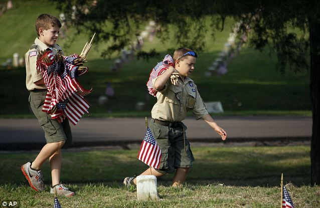 Service: Carrying small American flags, two Boy Scouts look for any grave markers without a flag in the Vicksburg National Cemetery in Vicksburg, Mississippi