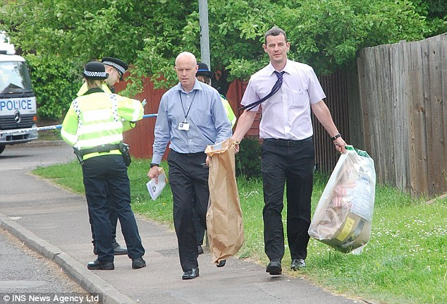 Evidence: Police pictured moving bags of evidence from the scene in May