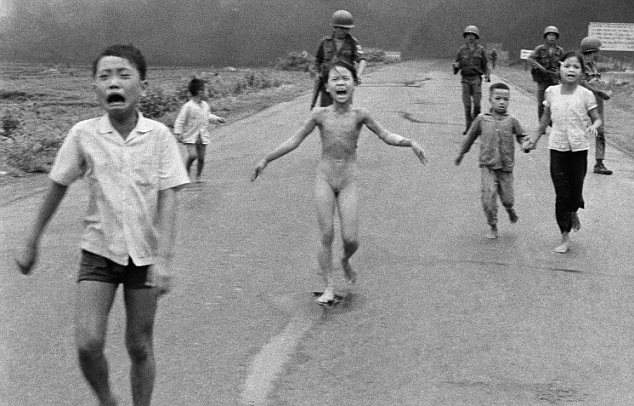 Crying children, including 9-year-old Kim Phuc, center, run down Route 1 near Trang Bang, Vietnam after an aerial napalm attack on suspected Viet Cong hiding places as South Vietnamese forces from the 25th Division walk behind them