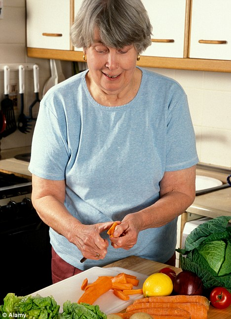 A6JYXT mature woman in kitchen peeling healthy vegetables