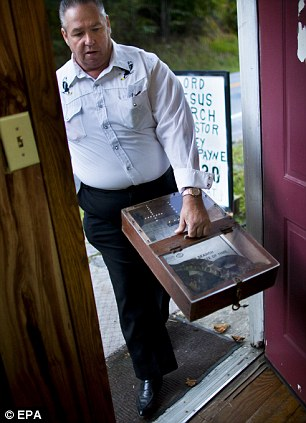 Rufus 'Buddy' Jewell (left) brings his snake box, which holds a giant timber rattlesnake, into the Church of the Lord Jesus