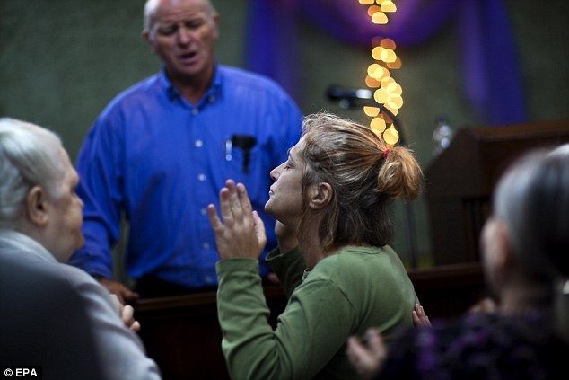 A visitor to the Church of the Lord Jesus, prays after being anointed with oil