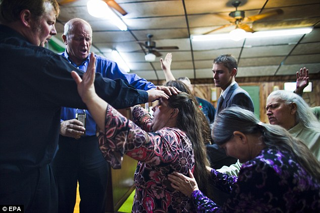 Pastors Harvey Payne (left), and Pete Woods (second to left) anoint a worshiper with oil