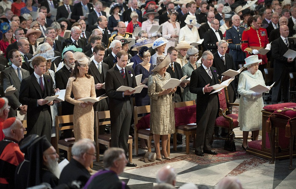 Sing song: The Queen and other members of the Royal family stand to sing hymns during the service