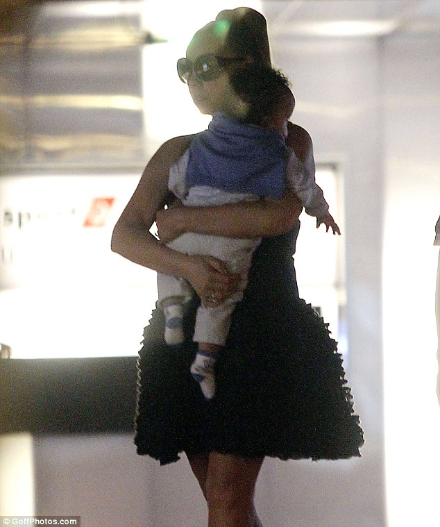 Snuggling: Mariah held her son close as they strolled round the airport