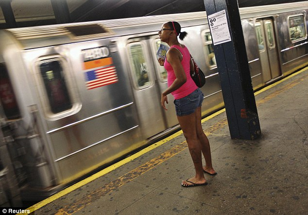Sweltering: A woman fans herself in the New York subway. Officials warned people to stay out the sun