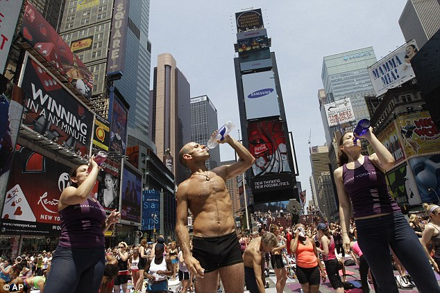 Staying hydrated: Yoga participants take a drink of water as temperatures inch towards triple digits