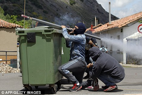 Striking Spanish miners fire homemade rockets towards Spanish Civil Guards in Cinera, near Oviedo, northern Spain, during a mass strike against subsidy cuts that they claim threaten tens of thousands of jobs