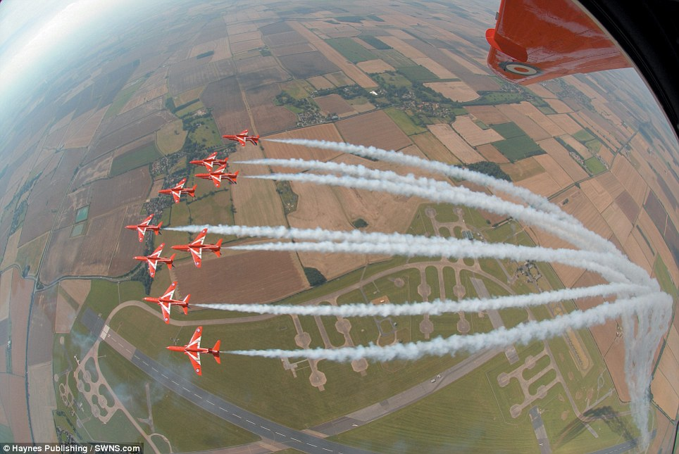On top of the world: The Red Arrows' signature vapour trails stripe the sky over an airfield