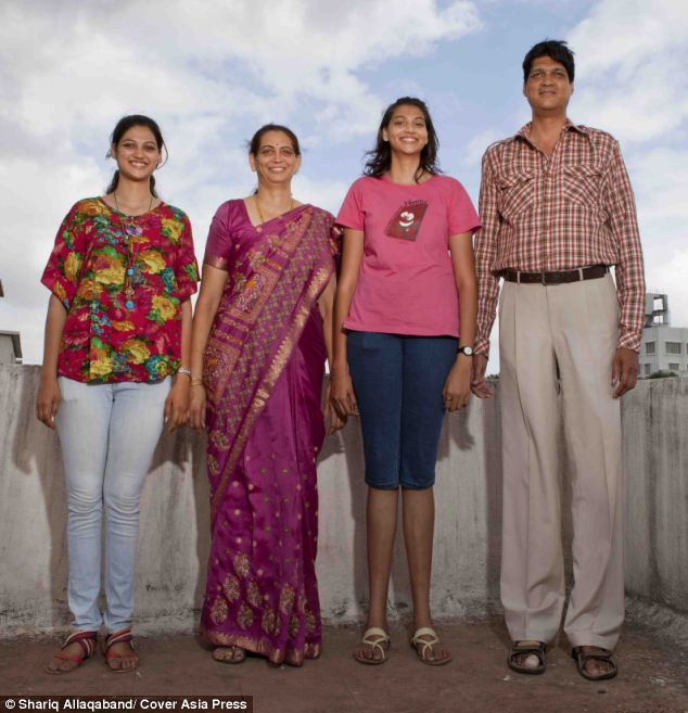 The Kulkarni family: Sharad (right) and his wife Sanjot (second left) and their daughters Sanya (left) and Mruga (right) stand a combined 26ft tall