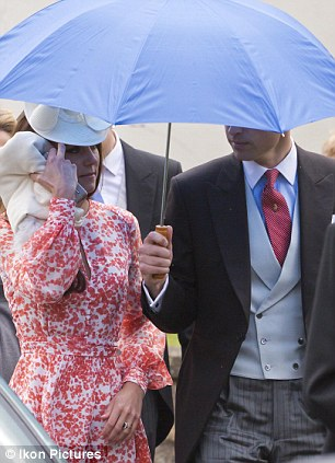 William, who looked smart in a morning suit, shielded his wife from the rain with an umbrella
