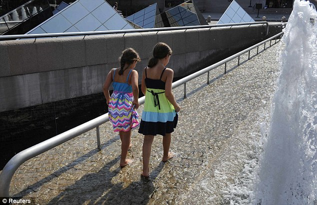 Cooling off: Girls paddle their feet in a fountain outside the National Gallery in Washington