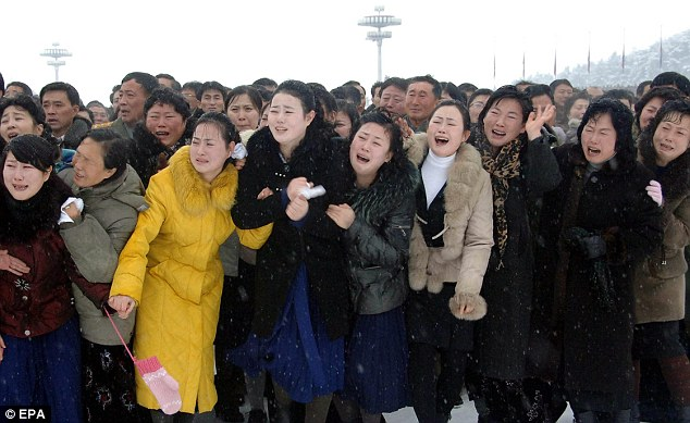 North Koreans wail theatrically after orders from military chiefs to break down in tears as they stand along the roadside during the state funeral procession of late North Korean leader last December