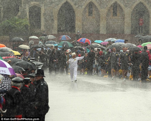 Olympic effort: The crowds gathered and so did the clouds at Windsor Castle today as the Olympic Torch was carried through an almighty downpour