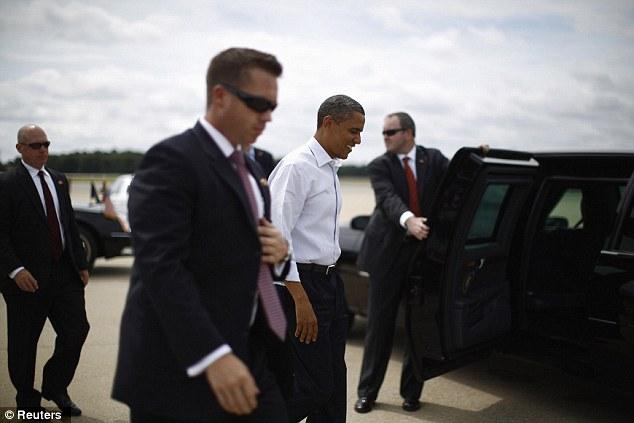 U.S. President Barack Obama walks to his limousine alongside Secret Service agents as he arrives at Norfolk Airport in Virginia, July 13, 2012