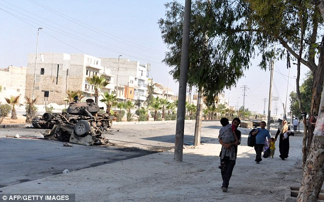 Unsafe: Syrian civilians leave their homes in Aleppo during a lull in fighting between opposition forces and army troops