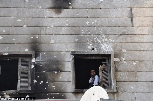 Un luchador libre del Ejército sirio se ve desde la ventana de la comisaría del distrito Shaar quemada en la norteña ciudad siria de Aleppo, después de haber sido invadida por los rebeldes el miércoles