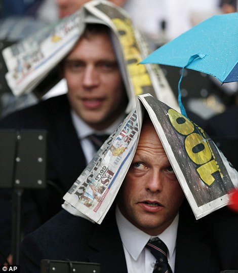 Spectators shelter from the rain with newspapers ahead of the Opening Ceremony at the 2012 Summer Olympics
