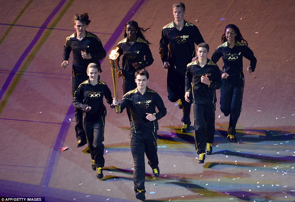 Young athletes carry the Olympic flame around the stadium