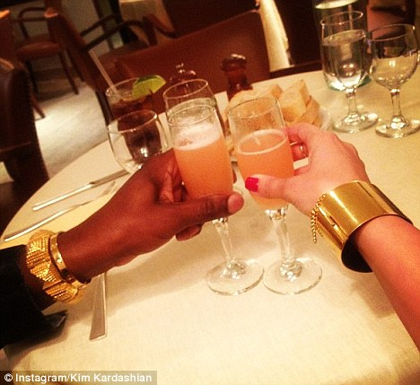 Kim Kardashian posted a picture of herself and boyfriend Kanye West enjoying a drink in New York while showing off their matching bracelets