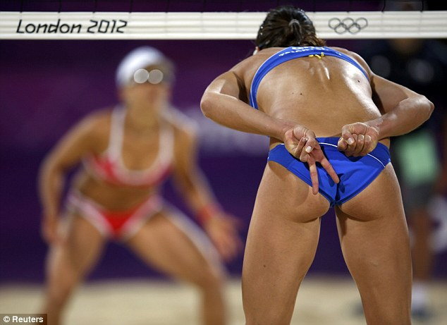 'Glistening like wet otters': Greece's Maria Tsiartsiani signals before serving to Switzerland's Nadine Zumkehr and Simone Kuhn during the women's beach volleyball, which has captured Boris Johnson's imagination