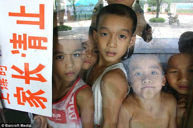 Home time: Children wait for their parents after completing a gymnastics training session in Nanning