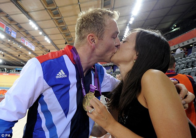 His proud partner then grabs a kiss from her medal-winning husband