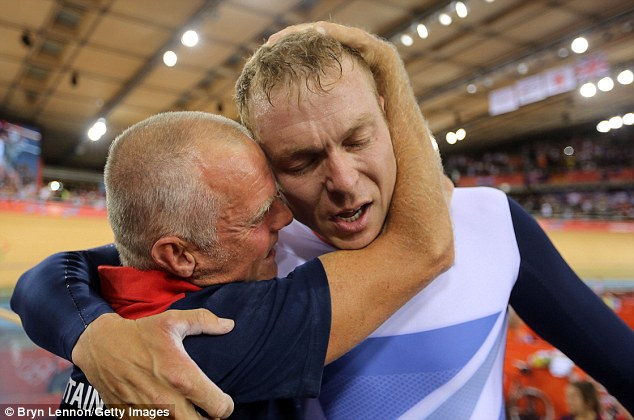 Record breaker: An exhausted Hoy celebrates with coach Shane Sutton at the side of the Velodrome track after his triumph in the Men's Team Sprint Track final
